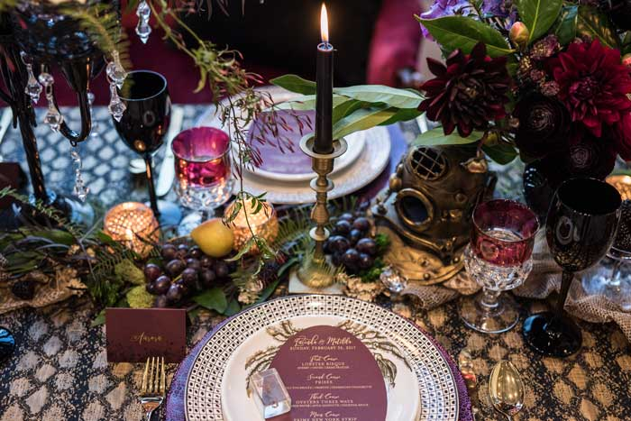 Haunting table design featuring dark and textural flowers, fruit, and oddities.
