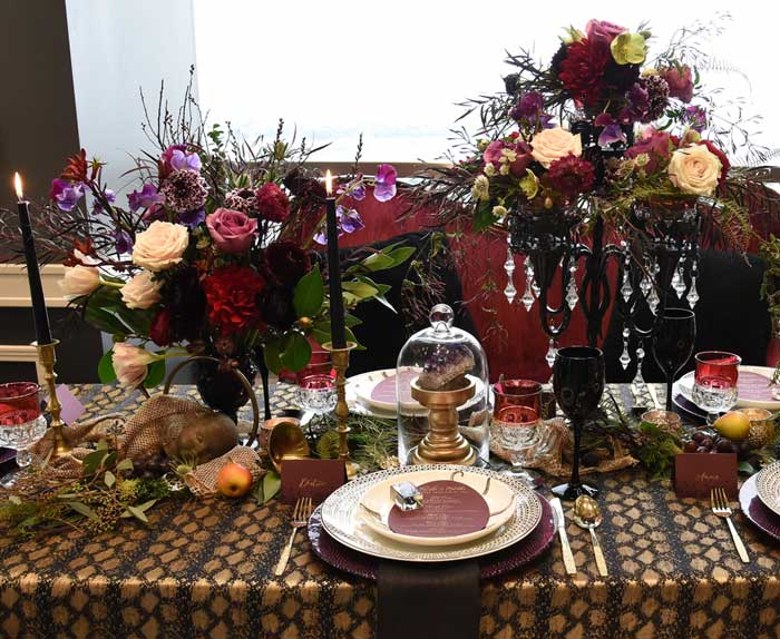 Halloween tablescape featuring dark florals, black tapers, and curious oddities.