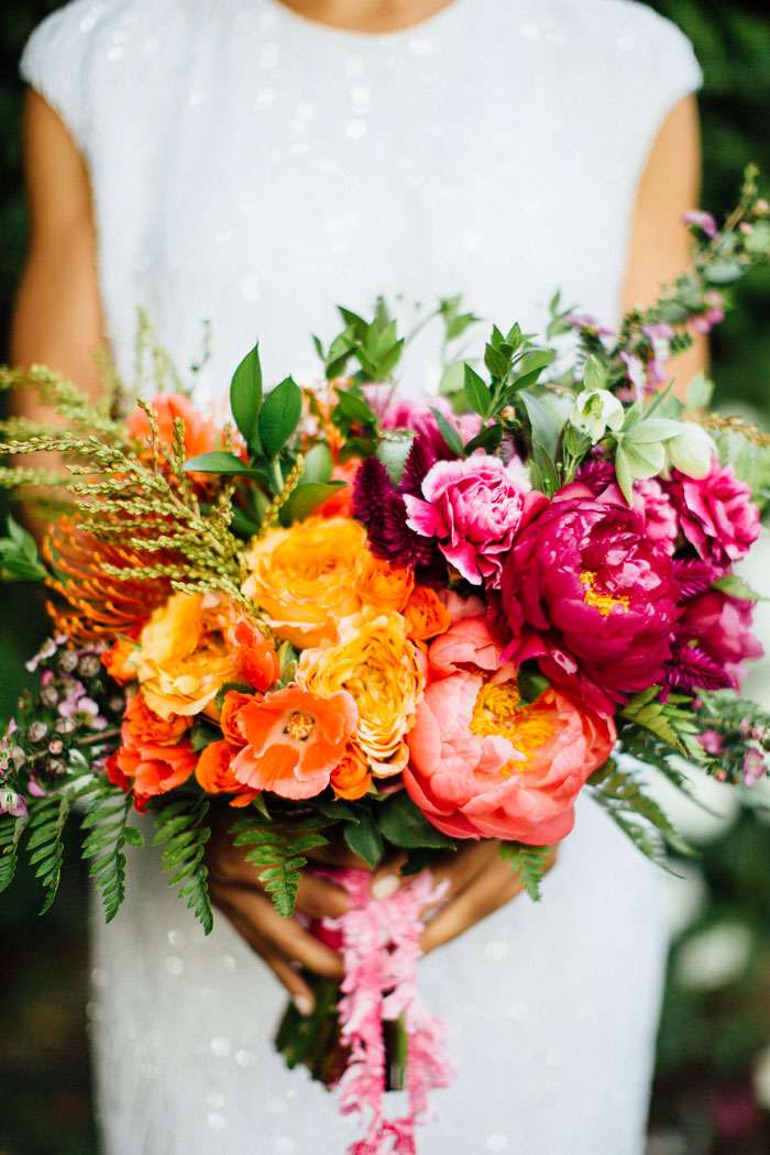 Brilliantly colorful bouquet featuring peonies, protea and ranunculus