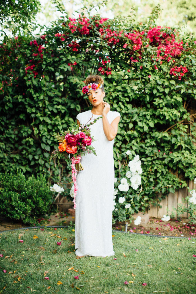 Beautiful bride with colorful floral headpiece and bouquet.