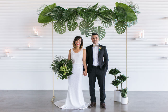 Cute wedding couple in front of modern tropical wedding arch with acrylic accents