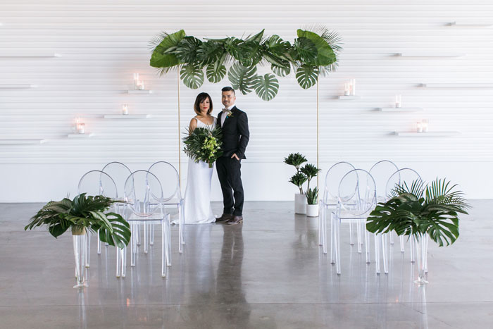 Modern, minimal, tropical wedding ceremony arch with monstera, banana leaves, elephant ear, and ghost chairs.