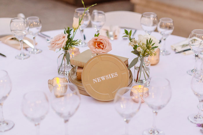 Romantic DTLA Library Wedding with centerpieces featuring garden roses, vintage books and film reel table names.