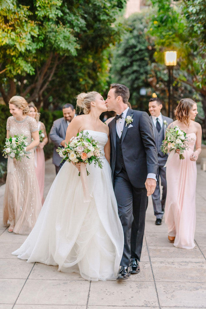 Cute wedding couple kissing, while walking with bridal party in DTLA.