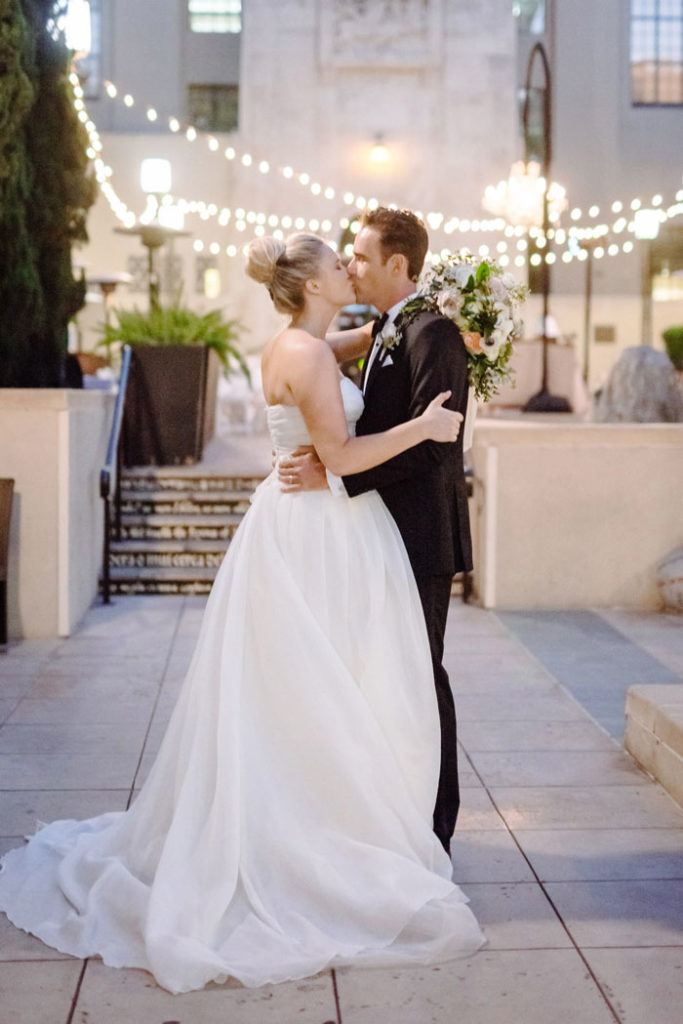 Couple kissing under cafe lights at romantic DTLA library wedding