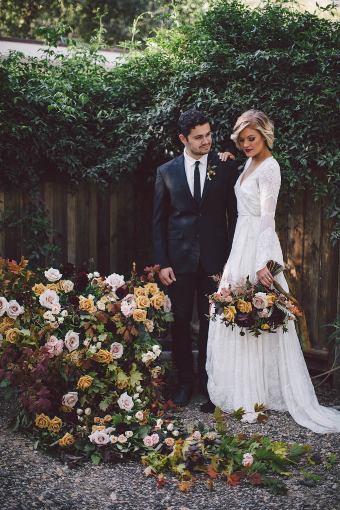 Boho couple pose next to rustic wheel barrow overflowing with fall flowers in shades of blush, gold, and berry