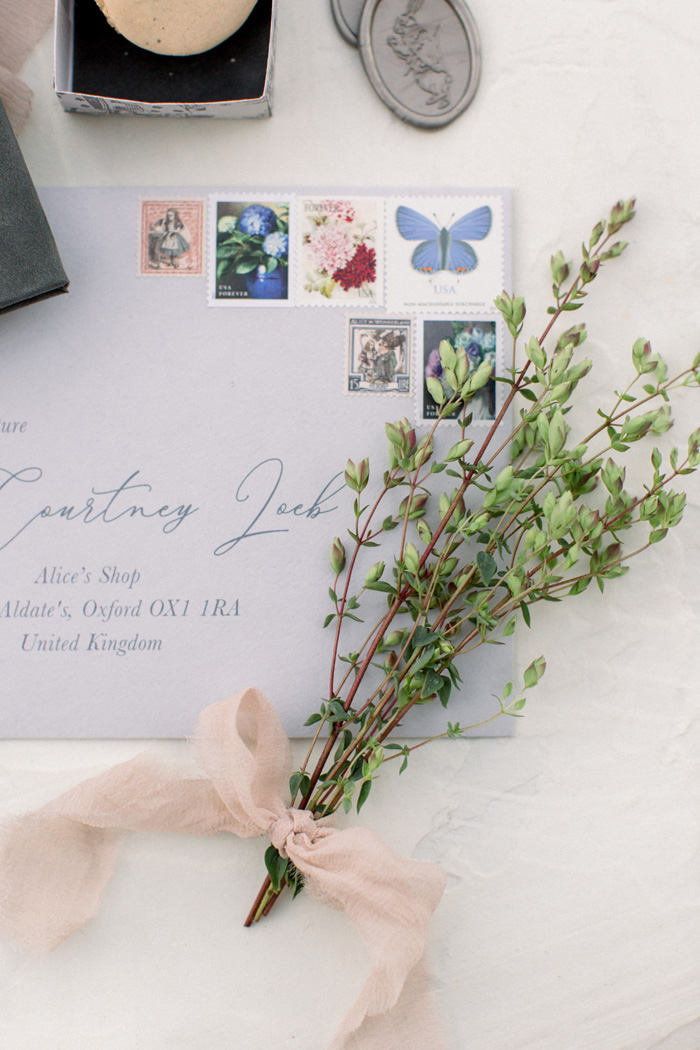 beautiful wedding envelope with calligraphy, vintage stamps, and fresh oregano