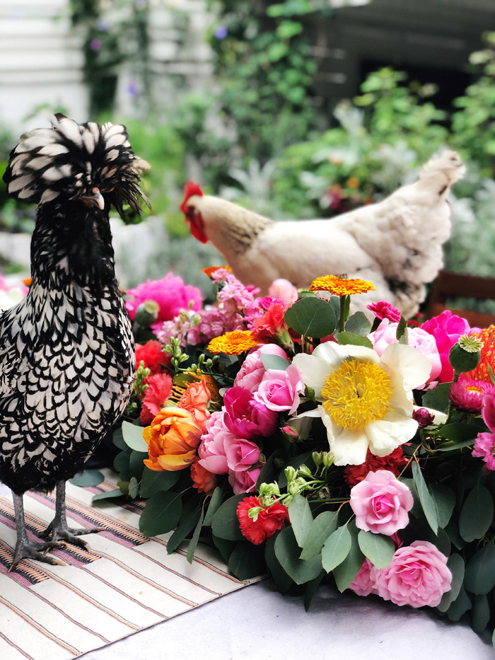 Backyard chickens frolicking in lush floral table garland