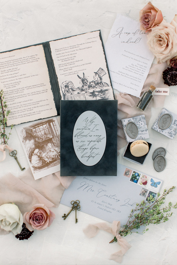 Alice in Wonderland invitation suite and flower flatlay