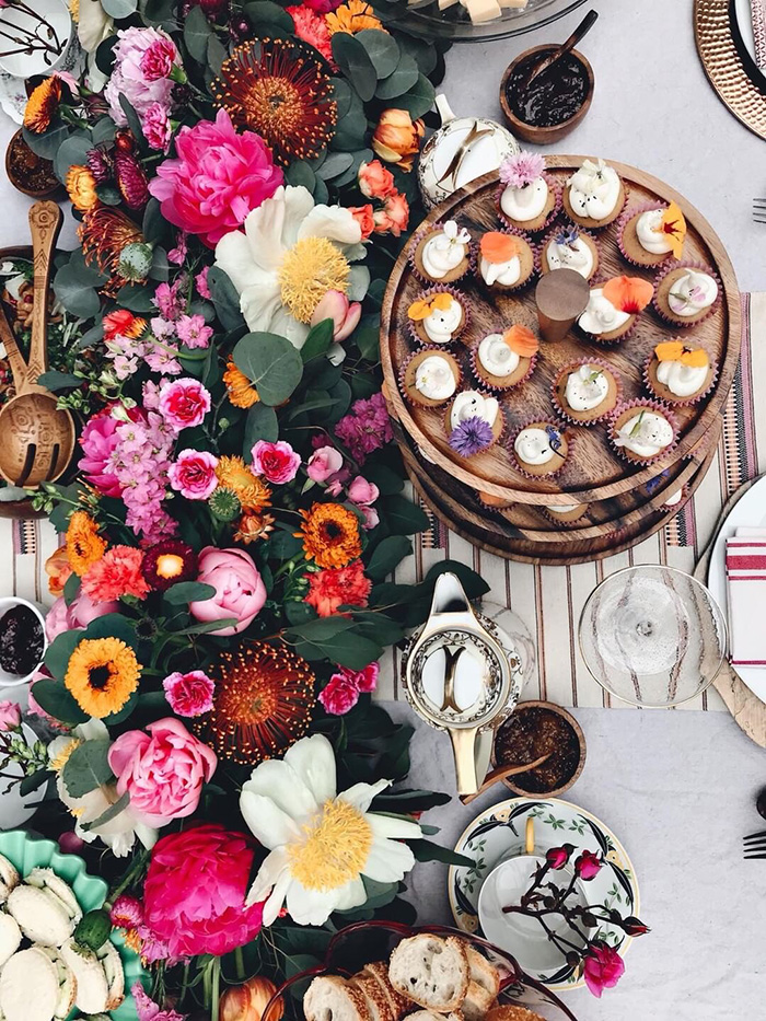 a birds-eye-view of a lush floral table garland and beautiful mini-cupcakes