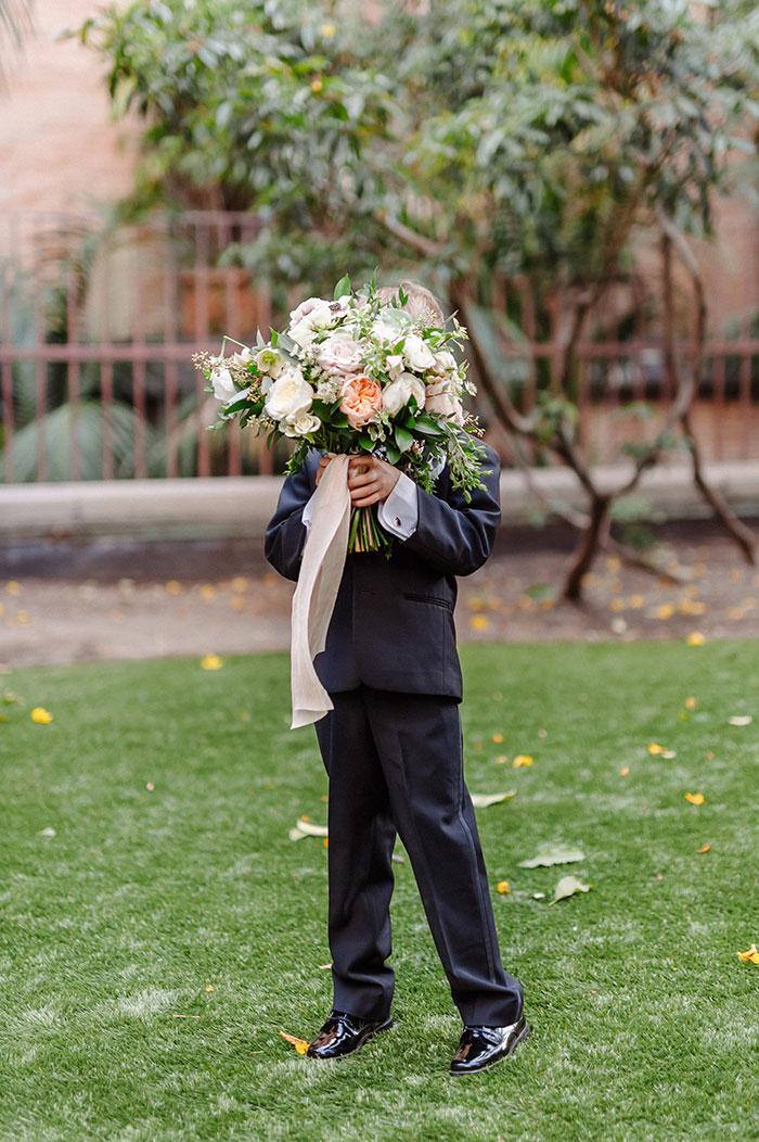 Cute ringbearer holding romantic bridal bouquet