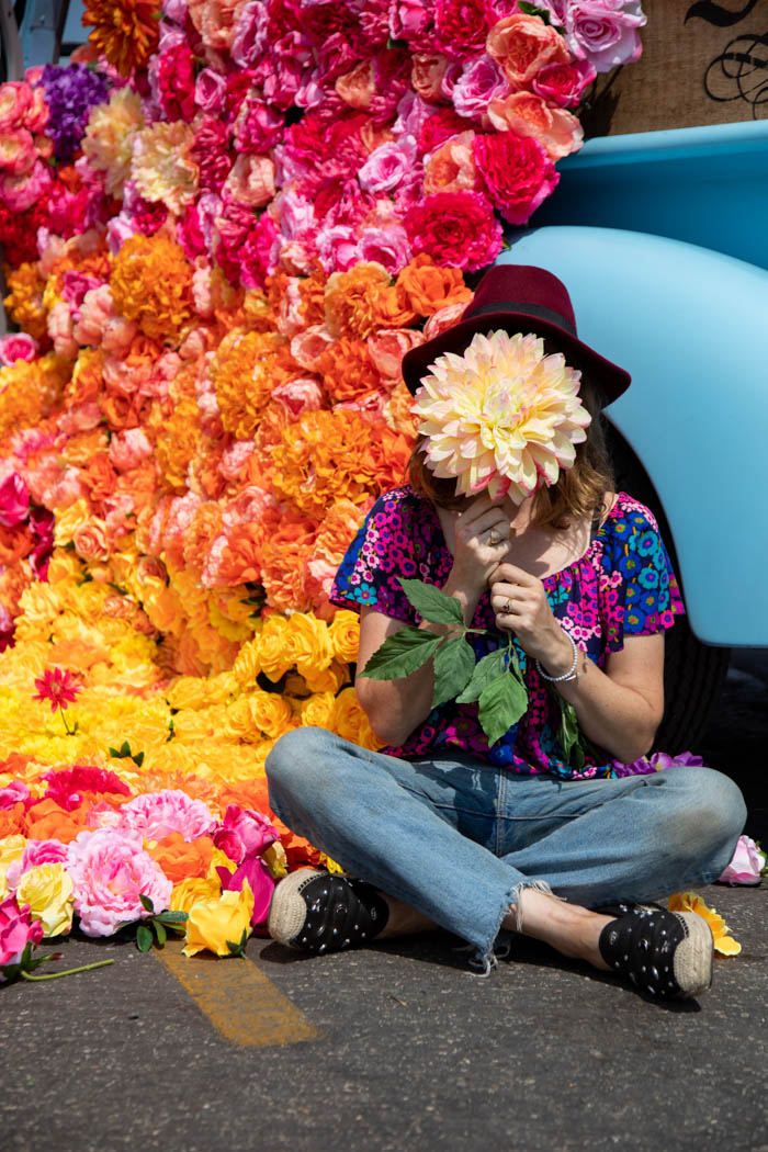 Tabitha Abercrombie of Winston & Main poses with a dinner plate dahlia and a backdrop of colorful flowers!