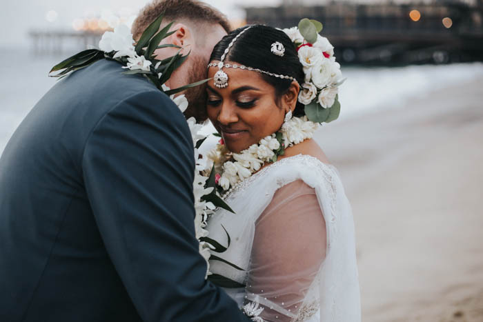 The cutest couple share an intimate moment on the beach for a private lei exchange featuring orchids, ti leaf, & tuberose following their wedding ceremony. The bride wears an ornate yet modern take on a Sri Lankan floral headpiece featuring ranunculus, spray roses, and eucalyptus.