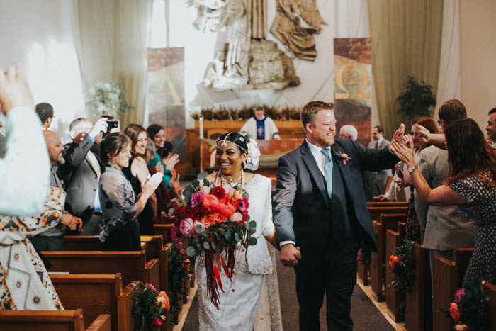 The cutest couple exit the church after their colorful wedding!