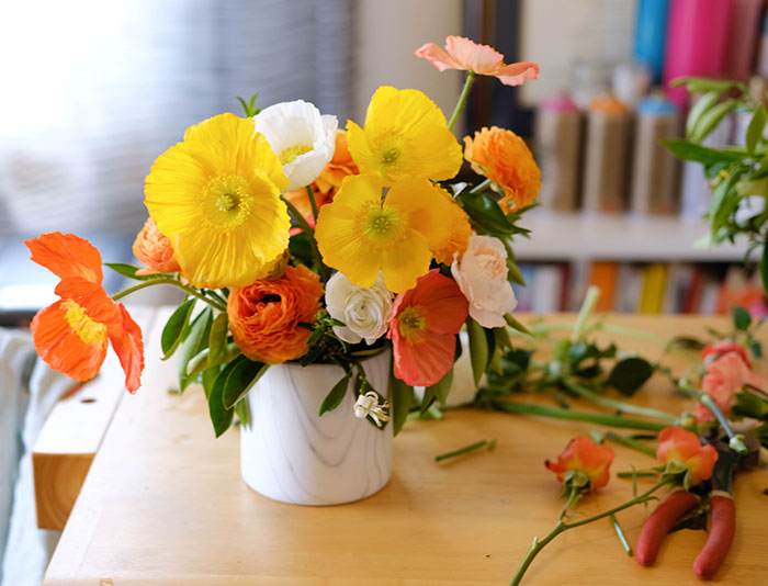 Beautiful arrangement by Winston & Main of yellow, orange, and white icelandic poppies and ranunculus in white marble vessel