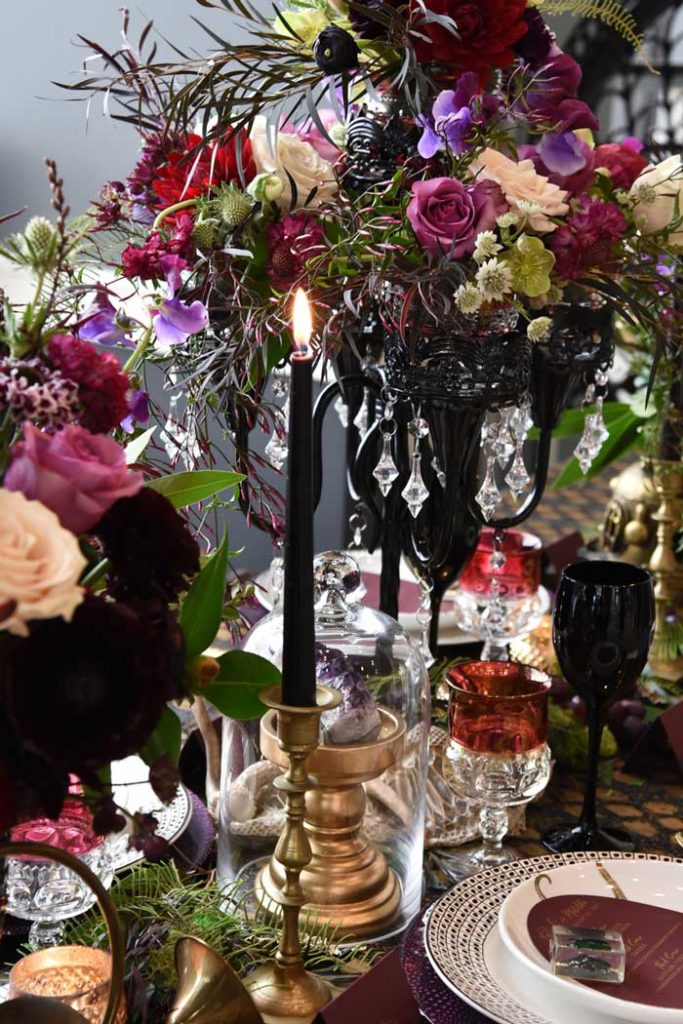 Halloween tablescape featuring dark and textural flowers, black tapers, and red and black goblets.