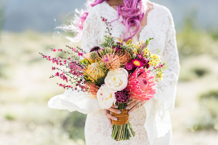 Bright, textural, and unique desert bridal bouquet featuring protea, peonies, and strawflowers.