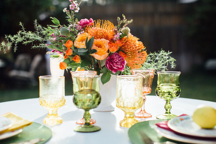 A colorful centerpiece and vintage glassware for a garden party