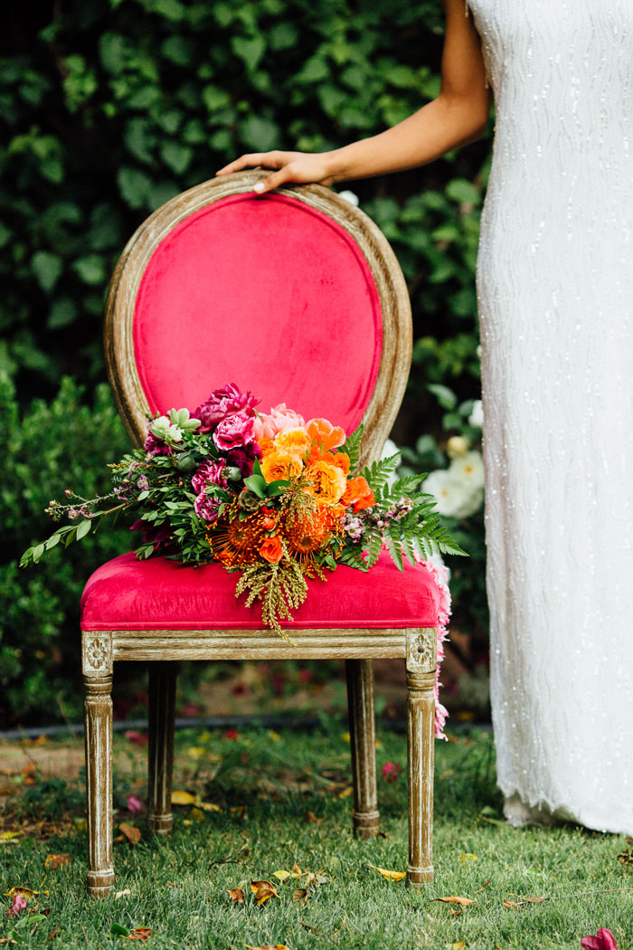 Colorful bridal bouquet resting on beautiful pink vintage chair.