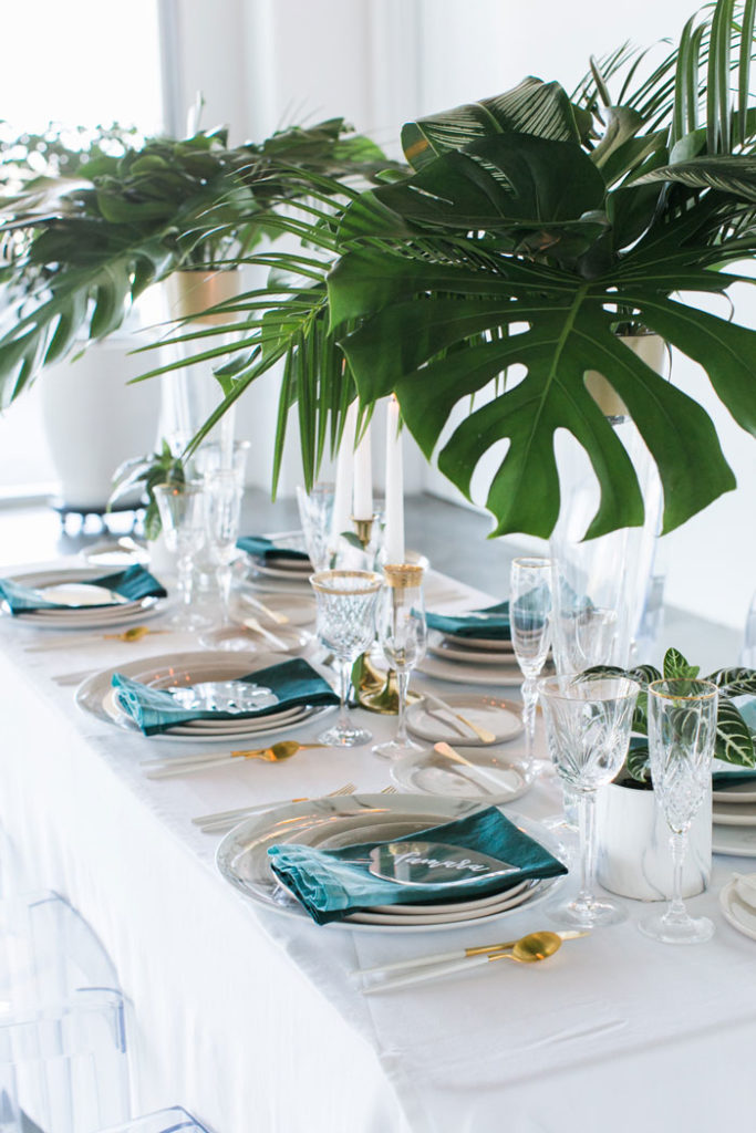 A modern tropical tablescape with tall centerpieces, and custom acrylic place cards.