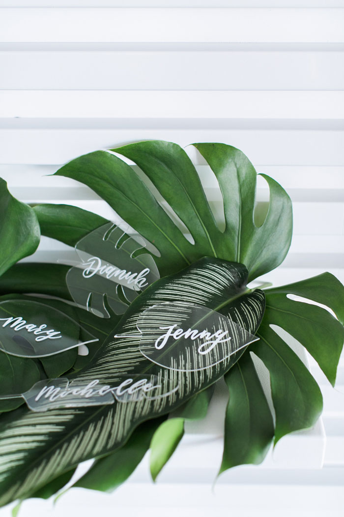 Tropical acrylic leaf escort cards by Winston & Main with calligraphy by Chasing Linen.