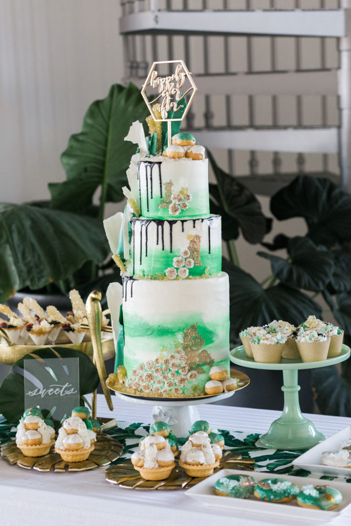 Tropical wedding dessert spread with bright green drip cake.