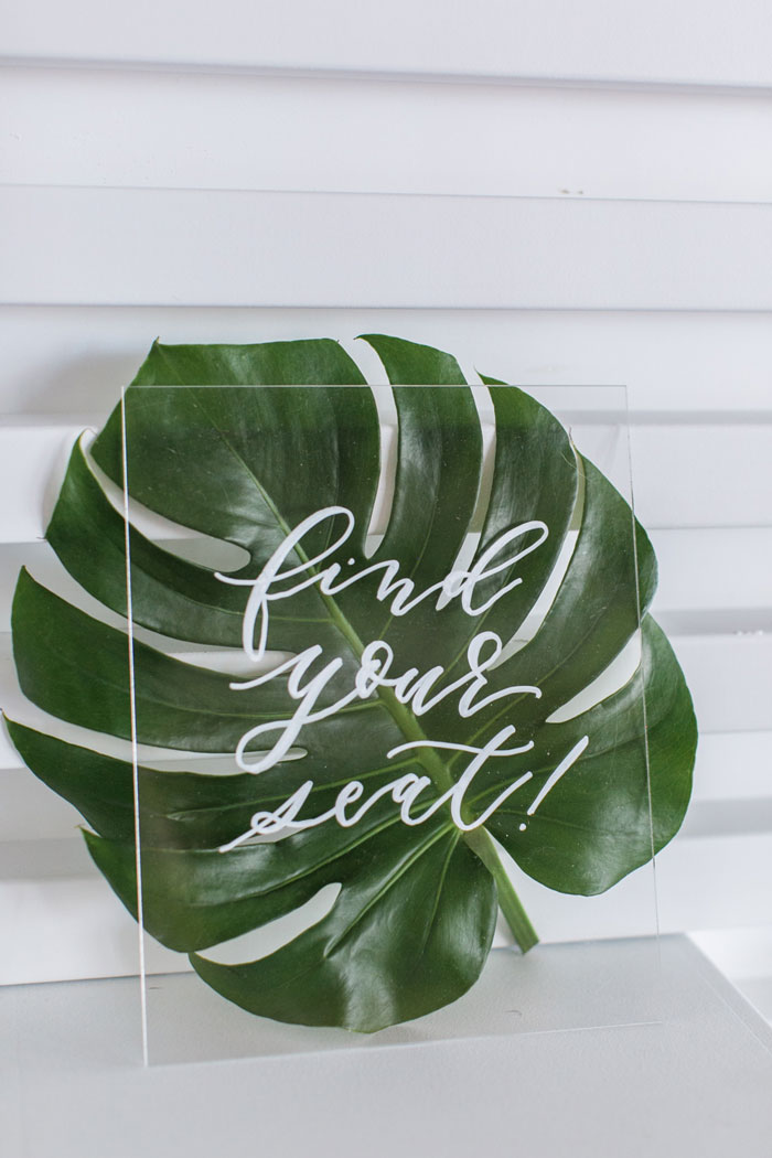 "Acrylic ""Find your Seat"" Sign with Monstera Leaf."