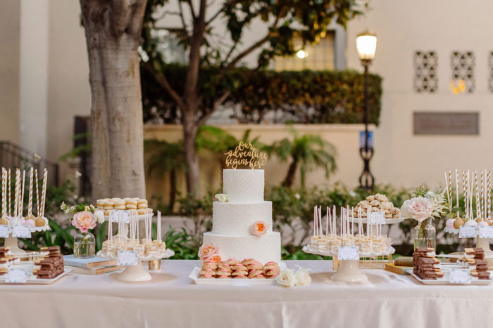 Beautiful desert table with cake, cake pops, and fresh flowers.