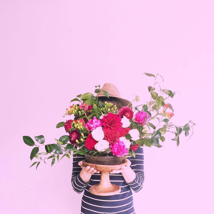 woman holding bright floral arrangement