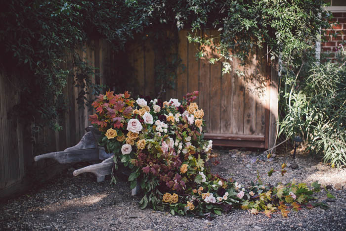 Installation in rustic wheel barrow with cascading fall flowers