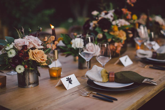 Rich fall tablescape featuring flowers in blush, berry, and gold