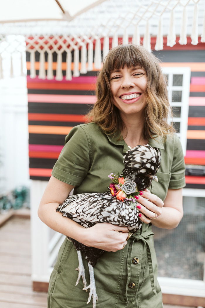 Winston and Main's Tabitha Abercrombie holding a polish chicken wearing a flower necklace