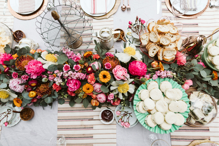 A birds-eye-view of a lush early summer floral garland on a table set for afternoon tea.