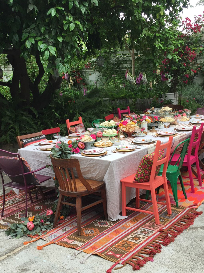 tablescape with overflowing garland and colorful chairs for garden party