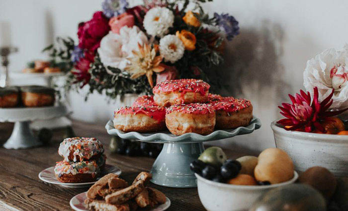 Decadent wedding spread including lush floral arrangement and delicious donuts.