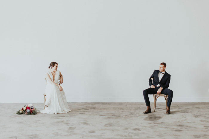 Sophisticated wedding portrait- cute couple sitting on rustic chairs.