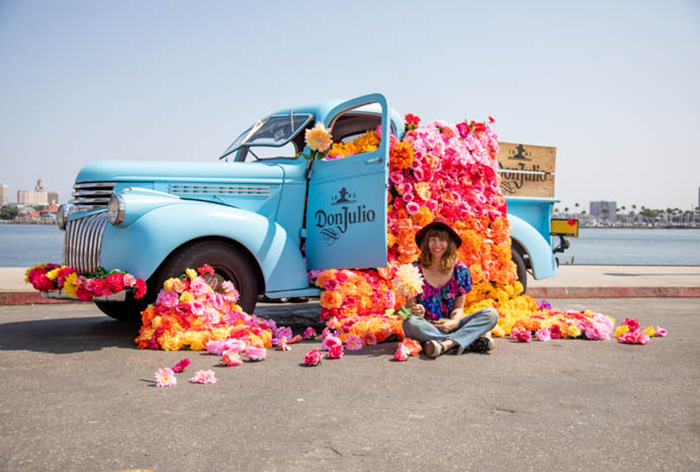 Tabitha Abercrombie of Winston & Main sits in front of her colorful floral installation for Don Julio Tequila.