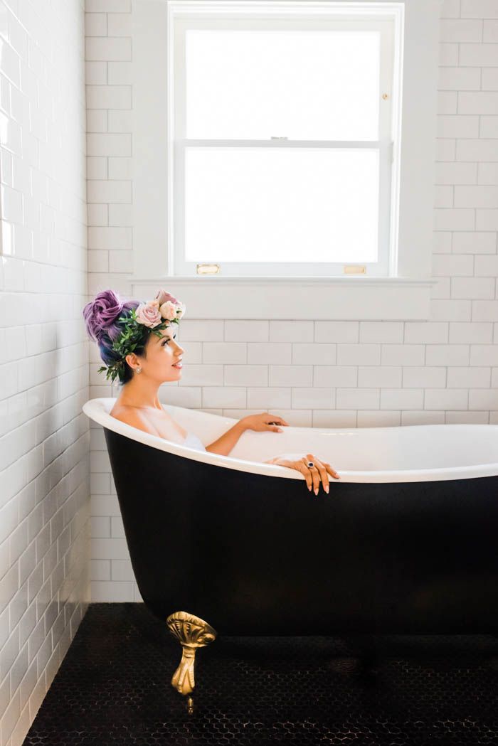 Unicorn mama-to-be in a black clawfoot bath tub surrounded by white subway tile.