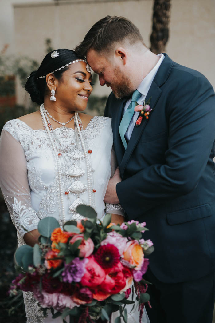 Romantic and colorful modern multicultural wedding couple share a sweet first look.