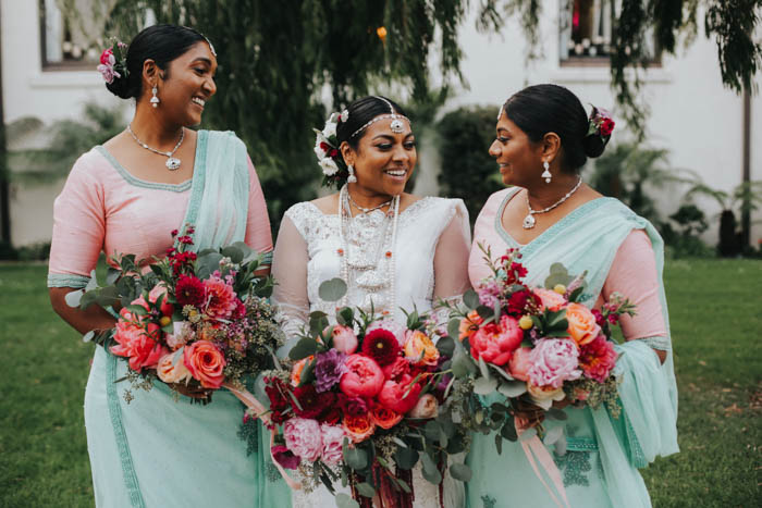 Beautiful bride and bridesmaids in white, peach, and mint saris carrying bold, colorful, and luxurious blooms.