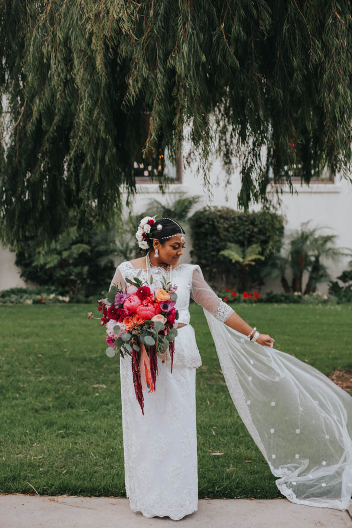 Modern Sri Lankan Bride with colorful, luxury bridal bouquet, beautiful hair flowers, and a gorgeous flowing veil.