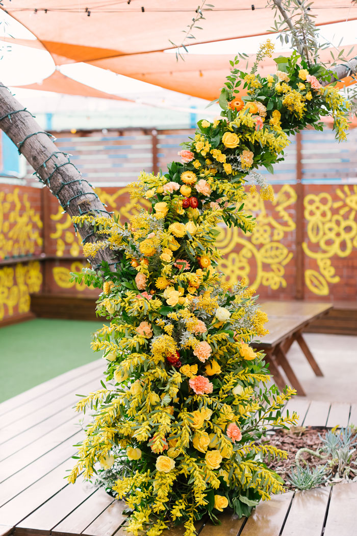 A brilliant foam-free floral installation climbs up a tree in the center of the reception space.