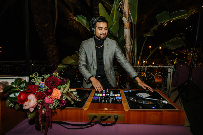 The DJ booth at our Houdini Estate wedding with moody jewel toned flower arrangements by Winston and Main