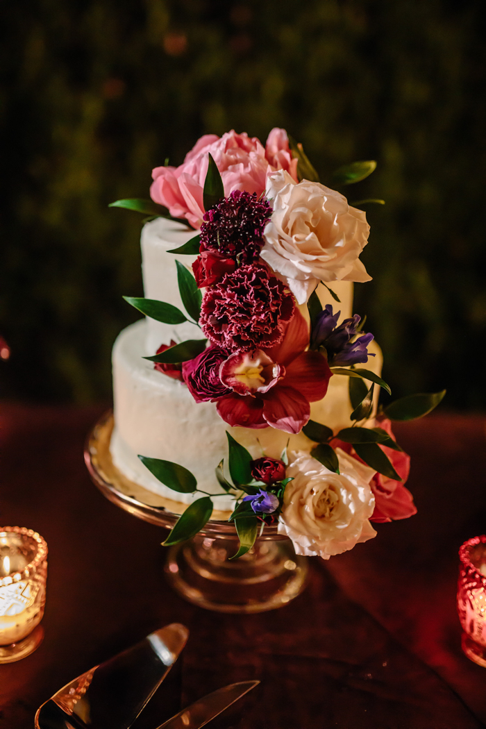 The romantic wedding cake with lush pink and red flowers decorated by Los Angeles florist Winston and Main