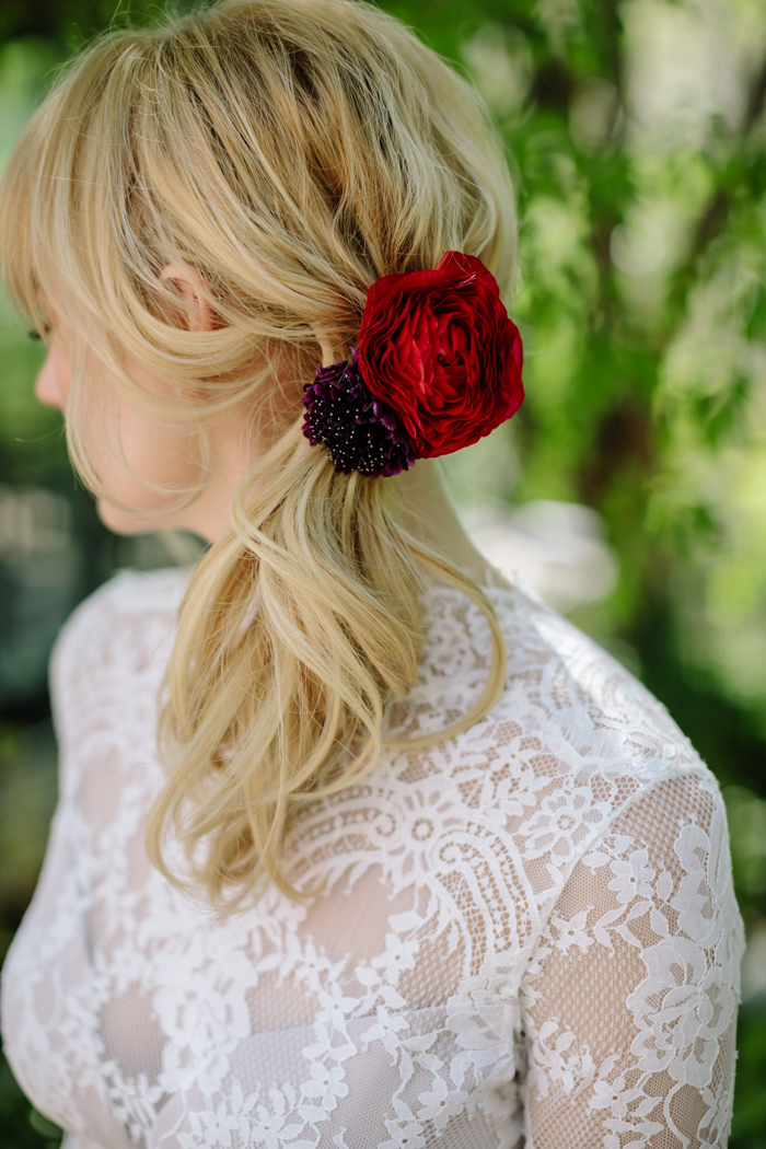 Bridal hair decorated with jewel toned flowers by Winston and Main.