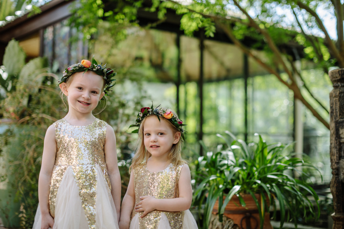 Two sweet flower girls in gold dresses wearing flower crowns by LA Florist Winston and Main.