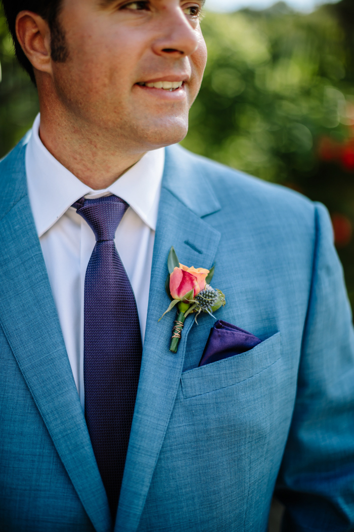 The jewel toned groom's boutonniere featuring a blue thistle and orange flower bud by Winston and Main