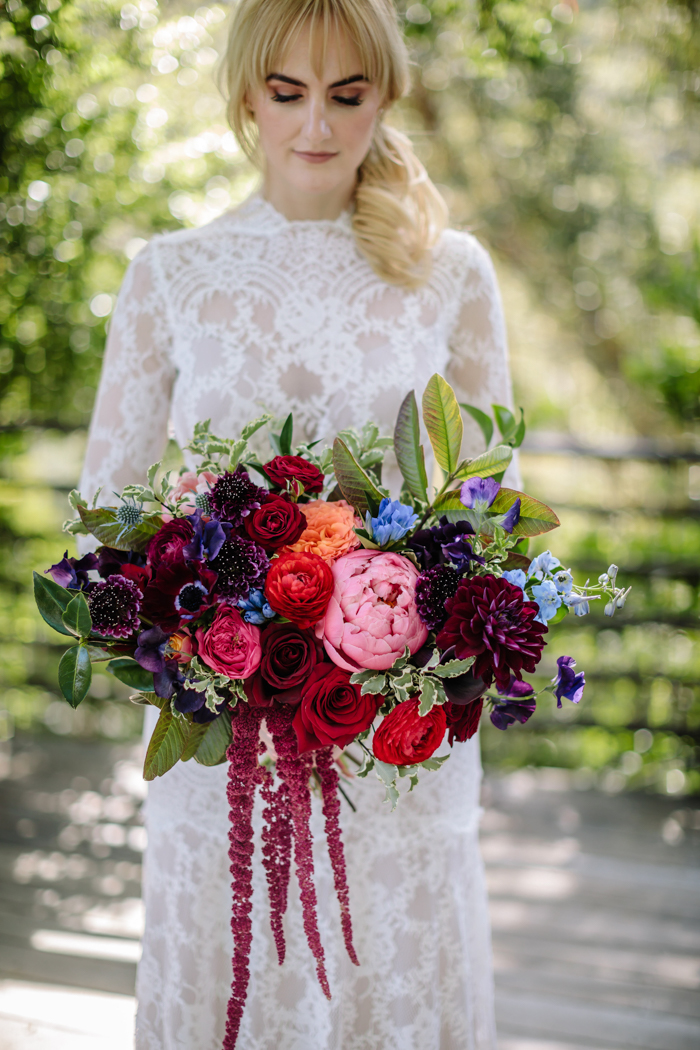 Our bride poses at Houdini Estate with her lush jewel toned bridal bouquet.
