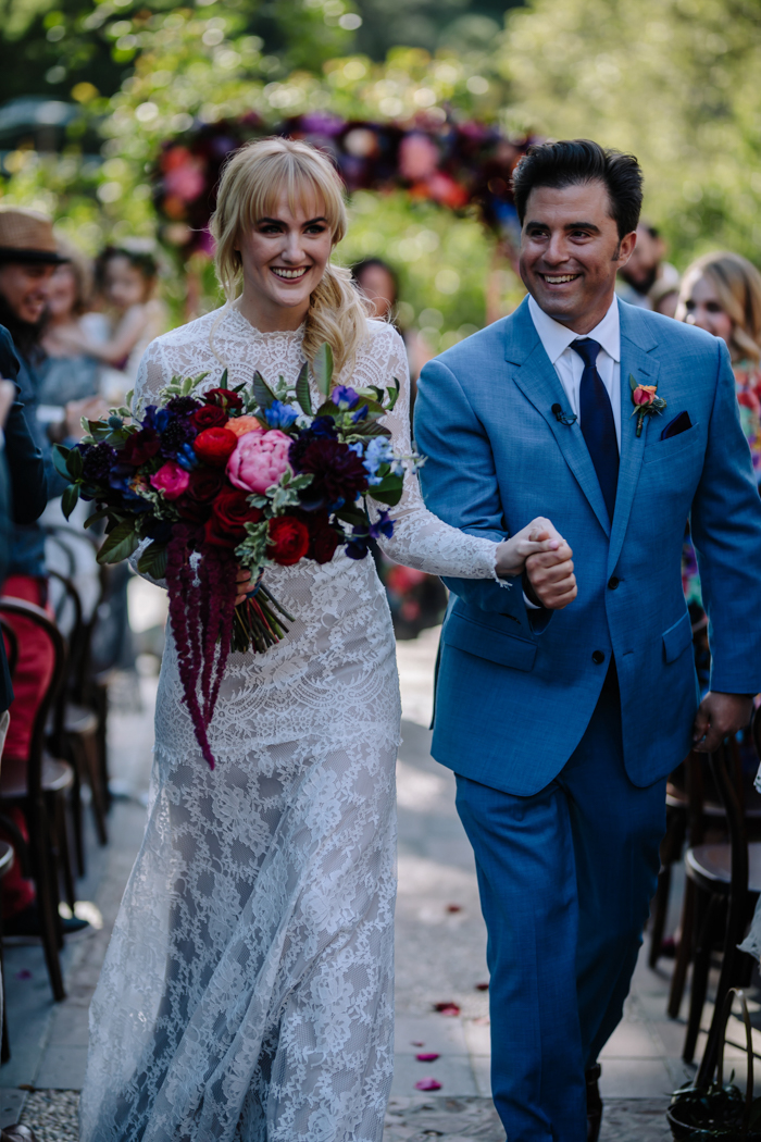 Our sweet newlywed couple walk down the aisle at their Houdini Estate wedding with jewel toned flowers designed by Winston and Main
