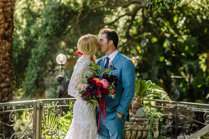Our sweet Los Angeles couple share a kiss at their Houdini Estate wedding with moody jewel toned flowers designed by Winston and Main